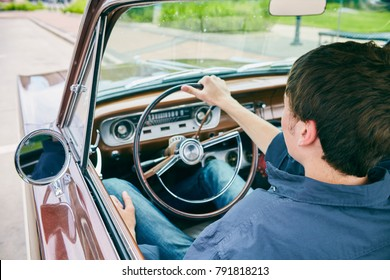 Rear view of young Caucasian man sitting at steering wheel and driving car