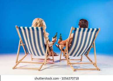 Rear view of young couple with beer bottles relaxing in deck chairs on blue background