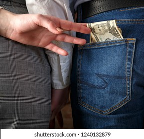 Rear View Of young couple holding hands, second hand wife pulls money from the pocket of her husband's