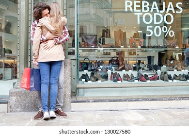 Rear view of a young couple hugging in a destination city while standing in the shopping district near a luxury shoe store, outdoors.