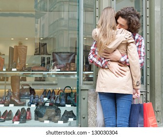 Rear view of a young couple hugging in a destination city while standing in the shopping district near a luxury quality shoe store, outdoors.