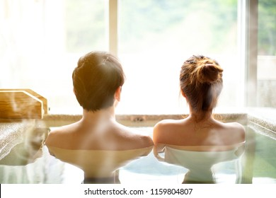rear view Young couple relaxing in hot springs