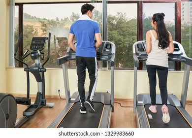 Rear view of young couple running on treadmills together in front of big window in fitness club