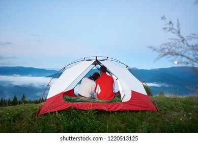 Rear view of a young couple sitting in a tent looking at the mountains in the morning haze at dawn under a blue sky on which the moon is shining in the distance.