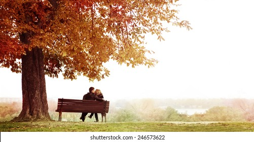 Rear View of Young Couple Sitting and Kissing on a Bench in the Beautiful Autumn Day . The man is embracing  her wife shoulder. Horizontal shot.