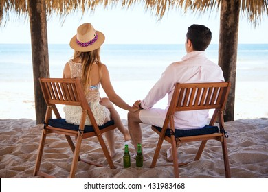 Rear view of a young couple sitting at the beach and enjoying the view while drinking some beer