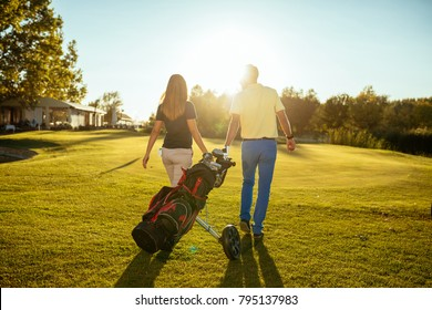 Rear view of a young couple walking on the golf coarse