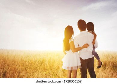 Rear view of young family embracing each other while looking at sunrise and standing together in the meadow