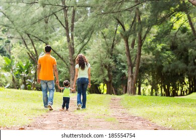 rear view of young family holding hands walking in forest