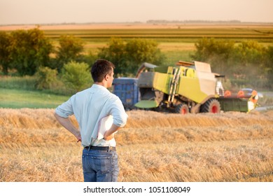 Rear view of young farmer engineer with notebook standing on wheat field while combine harvester working in background