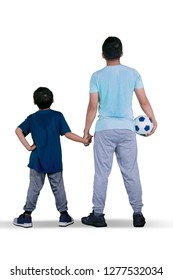 Rear view of young father and his son standing in the studio while holding a soccer ball, isolated on white background