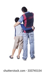 Rear view of a young father and his son embracing each other while looking at copy space in the studio