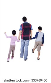 Rear view of a young father and his children holding hands in the studio and walking together