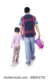 Rear view of young father walking to school with his daughter while carrying backpack, isolated on white background