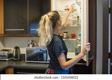 Rear view of a young female adult opening the fridge to get the milk out to make breakfast.