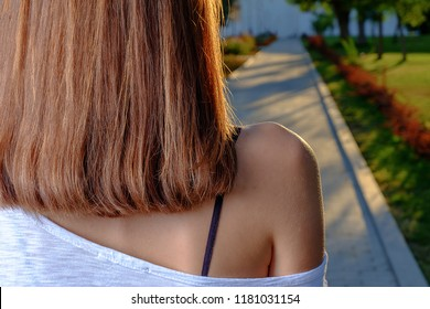 Rear view of the young female with ginger beautiful straight long hairs posing with bare shoulder looking at sunset alley