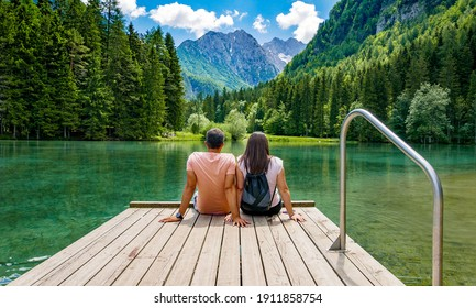 Rear view of young female sitting on wooden deck by beautiful lake in mountains  Green, spring, flower crown, outdoors  Zgornje Jezersko, Slovenia - Shutterstock ID 1911858754