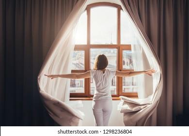 Rückblick - junge, passende Frau zu Hause Kleidung öffnet Vorhänge von Schlafzimmerfenster. Junge Mädchen ist bereit für neue Pläne und Herausforderungen. Konzept der Öffnung für die Welt, neue Angelegenheiten und neue Versprechen