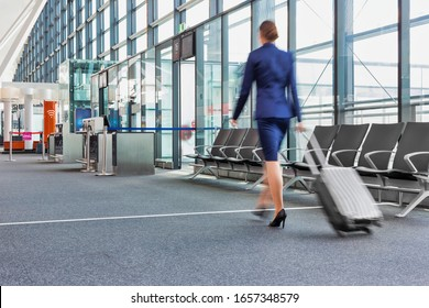 Rear view of young flight attendant walking in airport with lens flare