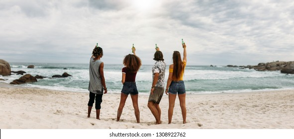 Rear view of young friends standing at the beach raising beer bottle at the sea. Group of friends having party celebrating and drinking at the beach.