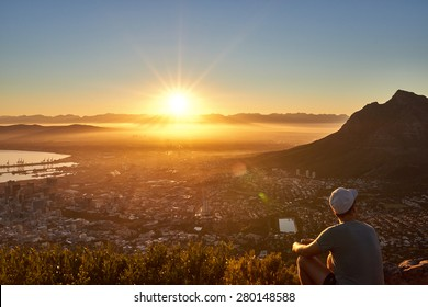 Rear view of a young guy sitting on a mountain trail watching the sunrise with the city below