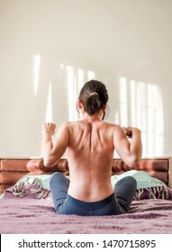 Rear view of young half-naked woman stretching muscles on the bed in the bedroom in the morning. Healthy lifestyle concept.