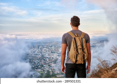 Rear view of a young hiker standing on a mountain path looking out over the city through the clouds