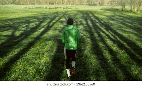 Rear view of a young jogger man running on green grass in the forest. Athletic male jogging in the park in the morning in a sunny day. People, healthy lifestyle and sport concept