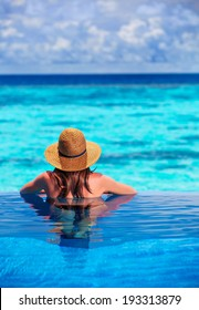 Rear view of young lady relaxing in the pool and enjoying view of beautiful seascape, refreshing in cool transparent water, summer holidays concept