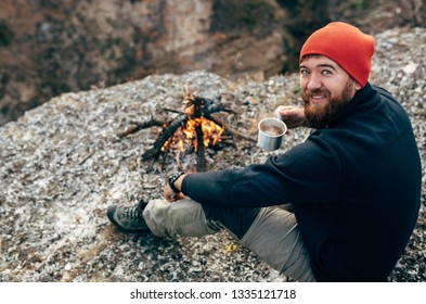 Rear view of young male drinking hot beverage in mountains near to bonfire. Traveler man in red hat, sitting and holding a mug of tea after hiking. Travel, sport, people and healthy lifestyle concept