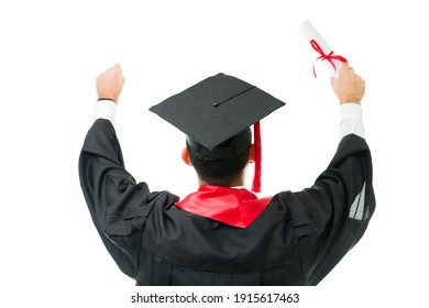 Rear view of a young male graduate with a gown and a cap raising his arms in the air as a celebration after getting a university certificate during a college graduation