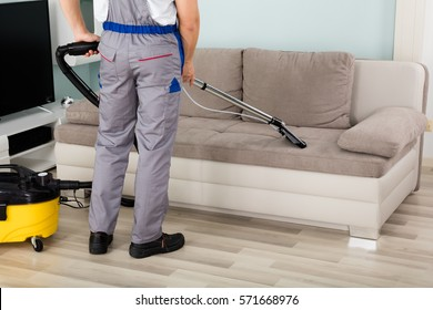 Rear View Of Young Male Worker Cleaning Sofa With Vacuum Cleaner