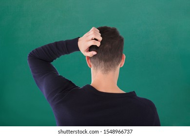 Rear View Of Young Man In Blue T-shirt Scratching His Head Against Green Background