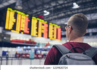 Rear view of young man checking flight schedule on the arrival departure board at airport.