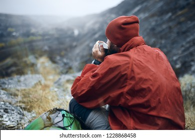 Rear view of young man drinking tea or coffee in mountains. Traveler man with beard and weraing red hat and jacket holding in hands a mug of tea, after hiking in moutain. Travel, lifestyle, vacation.