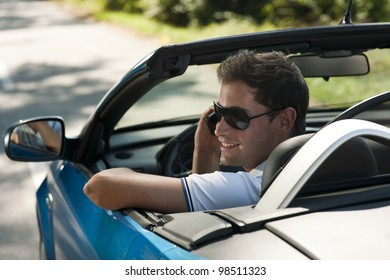 Rear view of a young man driving his convertible car