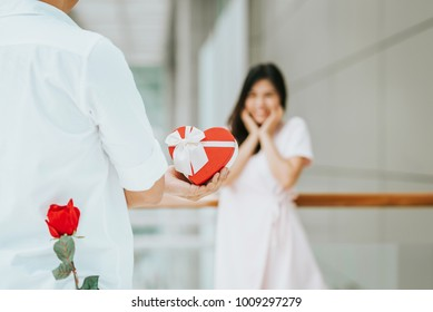 Rear view of a young man give present gift box with rose behind his back to his lovely girlfriend who look surprise