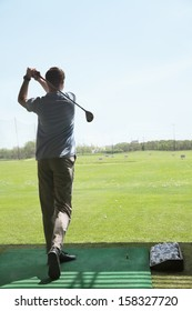 Rear view of young man hitting golf balls on the golf course
