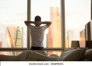 Rear view of young man looking at dawn city scenery in window after waking up. Handsome casual guy relaxing in penthouse in the morning with hands crossed behind his head. Motivation concept