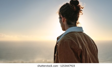 Rear view of young man overlooking sea. Man in warm jacket looking at view from mountain.