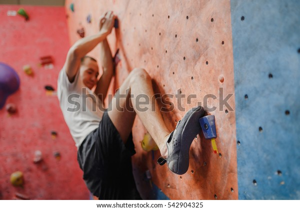 Rear view of a young man practicing in climbing at artificial wall in gym