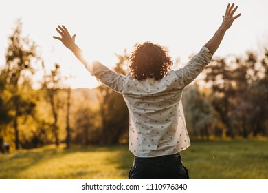 Rear view of young man rising hands up standing in the park enjoying beautiful sunset view. Outdoor shot of succesful student male feeling free. Caucasian prayer  man worship. People and lifestyle.