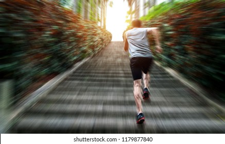 Rear view of young man running on stairs.