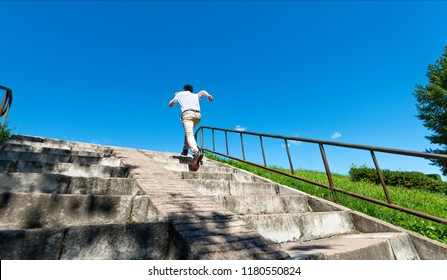 Rear view of young man running up on steps.