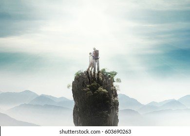 Rear view of a young man standing on the mountain peak with his son and looking at the sky