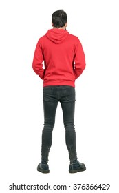Rear view of young man in tight jeans and boots wearing red hoodie. Full body length portrait isolated over white studio background.