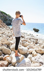 Rear view of young man using old photographic camera to take pictures beach landscape, practicing photographic creative hobby, sunny outdoors. Male holding camera, travel leisure recreation lifestyle.