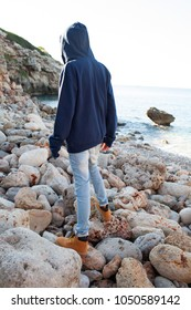 Rear view of young man walking on rocky beach on travel holiday, sunny outdoors. Teenager male enjoying nature, relaxing on vacation. Healthy well being leisure recreation lifestyle, texture exterior.