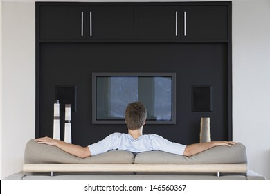 Rear view of young man watching television while sitting on couch in living room