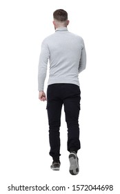 rear view. a young man in a white pullover walks forward